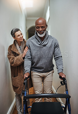 Buy stock photo Shot of a senior woman helping her husband to walk with his walker