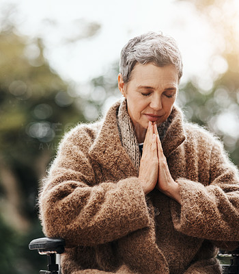 Buy stock photo Shot of a senior woman holding her hands together in prayer while sitting in her wheelchair outside