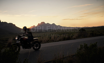 Buy stock photo Shot of a young woman riding her motorcycle through the countryside