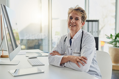 Buy stock photo Cropped portrait of an attractive mature female doctor sitting at her desk in the hospital