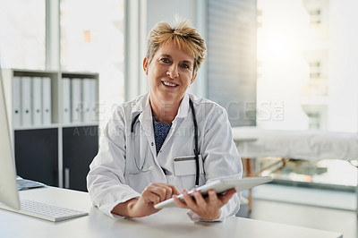 Buy stock photo Cropped portrait of an attractive mature female doctor working on a tablet at her desk in the hospital