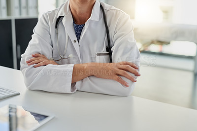 Buy stock photo Cropped shot of an unrecognizable female doctor sitting with her arms crossed at her desk in the hospital