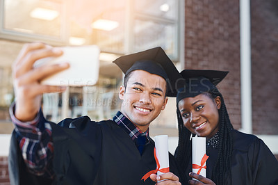 Buy stock photo Cropped shot of two students taking a selfie on graduation day