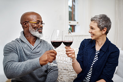Buy stock photo Shot of an affectionate senior couple enjoying some wine together at home