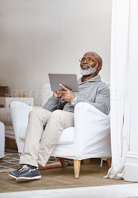 Buy stock photo Shot of a handsome senior man using his digital tablet while relaxing on a couch at home