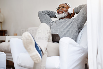 Buy stock photo Shot of a handsome senior man listening to music on a tablet while relaxing on a couch at home