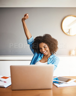 Buy stock photo Shot of an attractive young woman cheering with her arm raised while working on her laptop at home