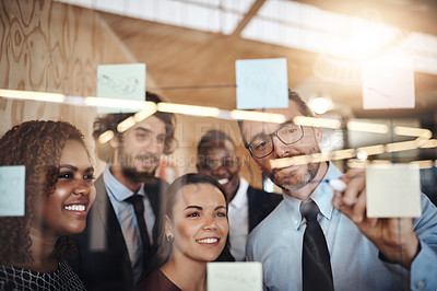 Buy stock photo Shot of a group of colleagues brainstorming together on a glass wall in an office