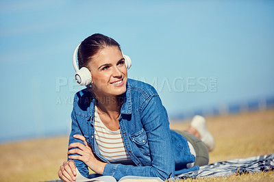 Buy stock photo Shot of an attractive young woman using headphones while relaxing in the park