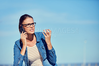 Buy stock photo Shot of an attractive young woman using a mobile phone outdoors and looking angry