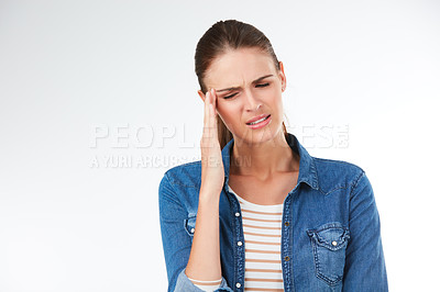 Buy stock photo Studio shot of a young woman suffering from a headache against a grey background