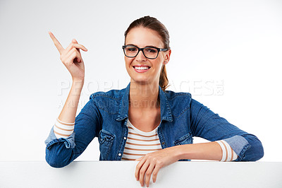 Buy stock photo Studio portrait of a young woman posing with a blank placard and pointing against a grey background