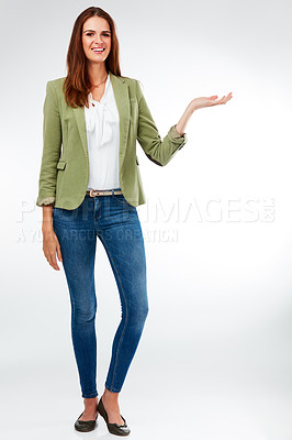 Buy stock photo Studio portrait of an attractive young woman presenting copy space against a grey background
