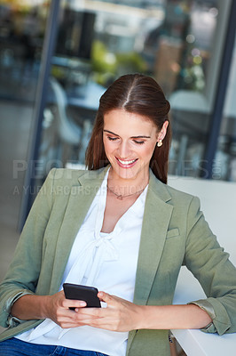 Buy stock photo Shot of a young businesswoman using a mobile phone in a modern office