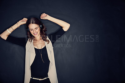 Buy stock photo Studio shot of an attractive young woman listening to music while posing against a dark background
