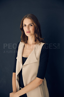 Buy stock photo Studio shot of an attractive young woman posing against a dark background