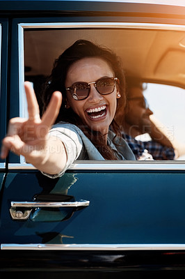 Buy stock photo Cropped portrait of an attractive woman giving you a peace sign while enjoying a roadtrip
