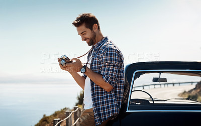 Buy stock photo Shot of a man looking at his camera while out on a road trip