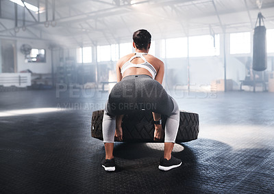 Buy stock photo Shot of young women lifting a tyre in the gym