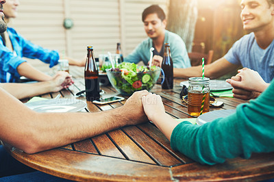 Buy stock photo Cropped shot of a group of friends saying grace before enjoying their lunch together