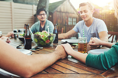 Buy stock photo Shot of a group of young friends holding hands together around a table outside in a garden