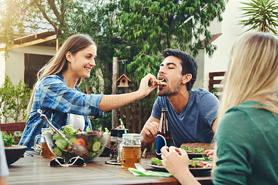 Buy stock photo Shot a cheerful young man being fed pizza by his girlfriend in an outdoor gathering amongst friends