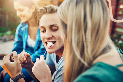 Buy stock photo Shot of a young cheerful man being fed a marshmallow by his girlfriend while relaxing outside with friends