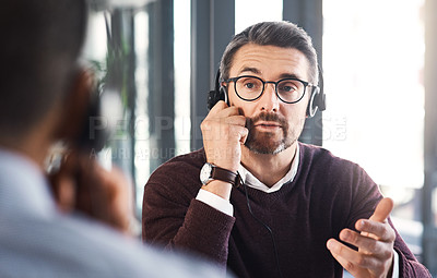 Buy stock photo Shot of a call centre agent talking to his colleague in an office