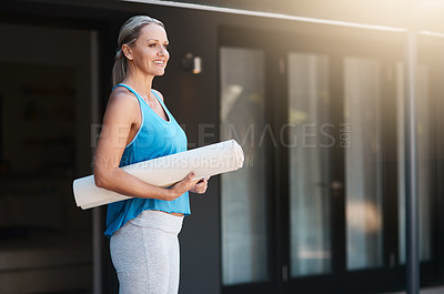 Buy stock photo Shot of a mature woman smiling and holding her yoga mat outside of her home in the morning