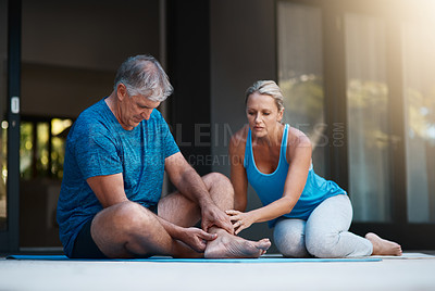 Buy stock photo Shot of a mature man holding his ankle in pain after an intense workout session with his wife