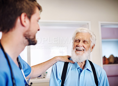 Buy stock photo Shot of a young doctor putting his hand on a senior man's shoulder in comfort at a clinic
