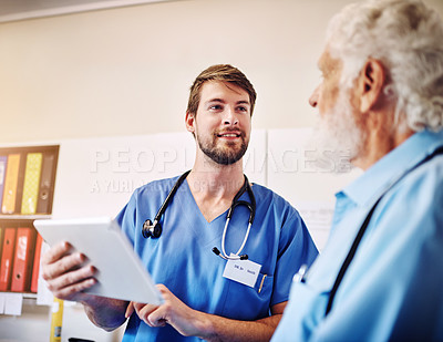 Buy stock photo Shot of a young doctor using a digital tablet to explain a diagnostic to a senior patient at a clinic