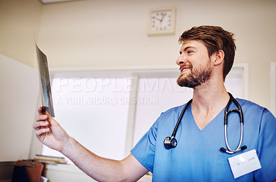 Buy stock photo Shot of a young doctor analyzing an x-ray alone in his office
