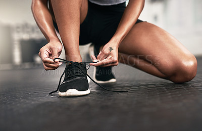 Buy stock photo Closeup shot of a sporty woman tying her shoelaces in a gym