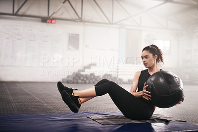 Buy stock photo Shot of a young woman working out with an exercise ball in a gym