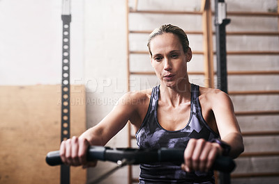 Buy stock photo Shot of a young woman working out on a rowing machine at the gym