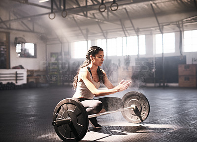 Buy stock photo Shot of a sporty young woman rubbing chalk powder on her hands to lift a barbell in a gym