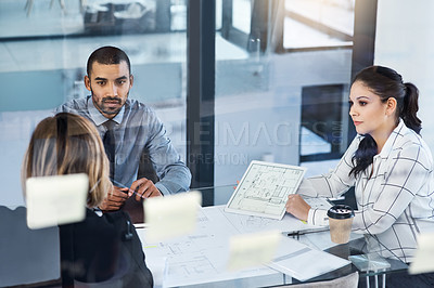 Buy stock photo Shot of a group of businesspeople analyzing blueprints in an office