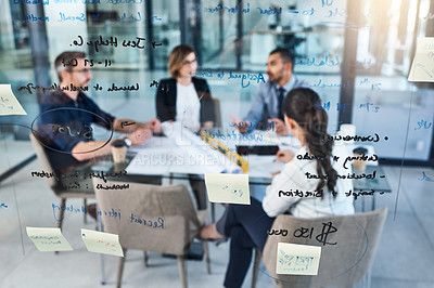 Buy stock photo Shot of notes on a glass wall with businesspeople having a meeting in the background in an office