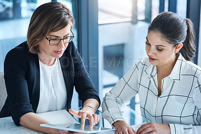 Buy stock photo Shot of two businesswomen working on a digital tablet together in an office