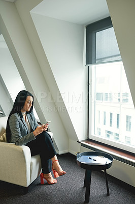 Buy stock photo Full length shot of an attractive young businesswoman using her cellphone while standing in the office