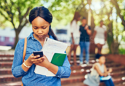 Buy stock photo Cropped shot of an attractive young female university student using her cellphone on campus with a few classmates in the background