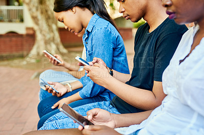 Buy stock photo Cropped shot of a group of young university students texting while sitting on a bench on campus