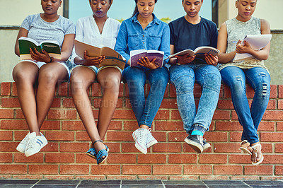 Buy stock photo Cropped shot of a group of young university students sitting with their books on a wall on campus