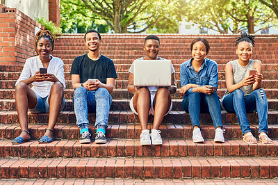 Buy stock photo Full length portrait of a group of young university students using their wireless devices while sitting on some stairs on campus