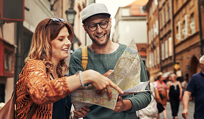 Buy stock photo Cropped shot of a young couple using a map while exploring a foreign city