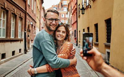 Buy stock photo Cropped shot of a young couple having their picture taken while exploring a foreign city