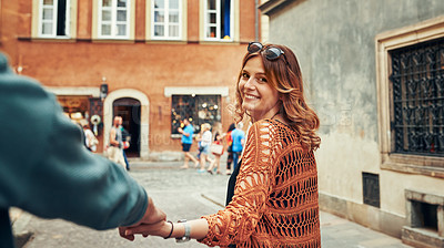 Buy stock photo Cropped shot of a young woman pulling her boyfriend's hand while exploring