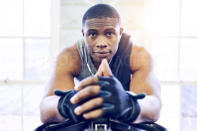 Buy stock photo Cropped portrait of a handsome young athletic man sitting on an exercise bike in the gym