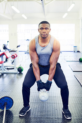 Buy stock photo Full length portrait of a handsome young athletic man working out with a kettle bell in the gym